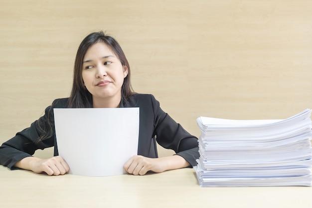 Closeup, femme de travail sont ennuyeux de pile de papier dans le concept de travail Photo Premium