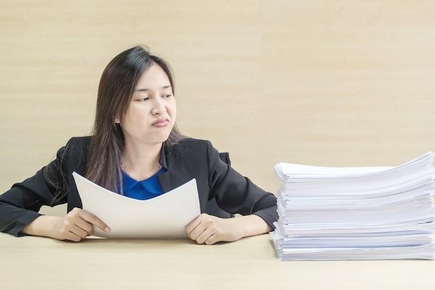 Closeup femme travaillant s'ennuyer de la pile de travail Photo Premium