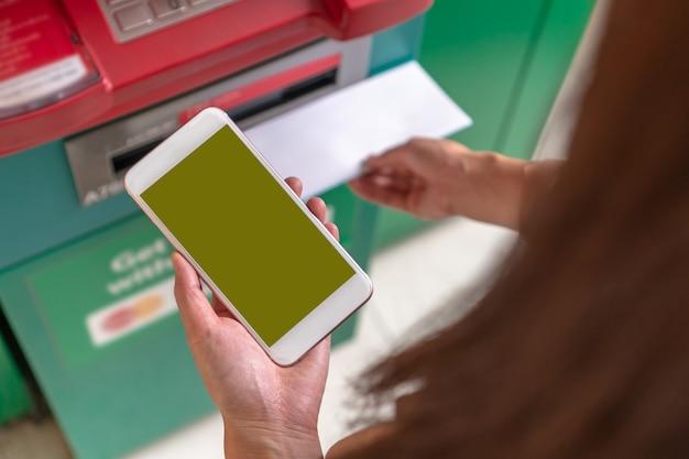 Closeup Femme Utilisant Le Téléphone Mobile Intelligent Pour Retirer L'argent Et Scanner Le Barco Photo Premium