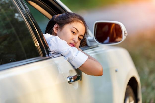 Closeup femmes asiatiques d'une voiture inquiète regardant de côté par la fenêtre dans une journée triste Photo Premium