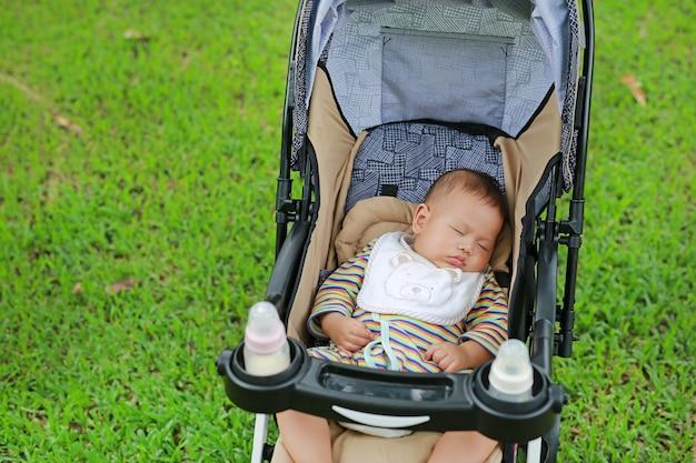 Closeup garçon asiatique nouveau-né dort dans la poussette sur le parc naturel. Photo Premium