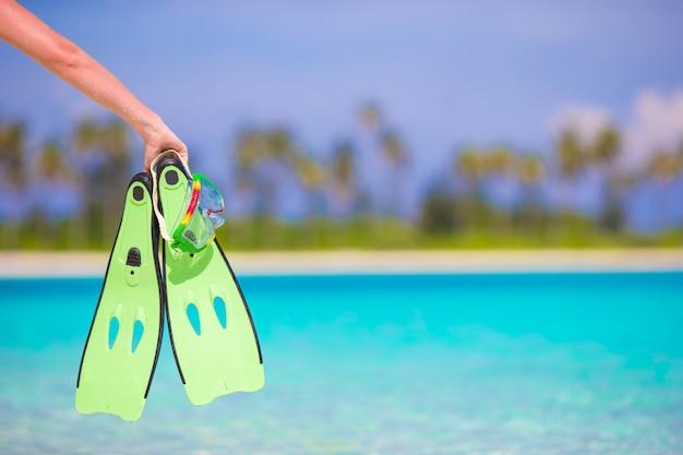 Closeup green fins dans une main féminine sur la plage blanche Photo Premium