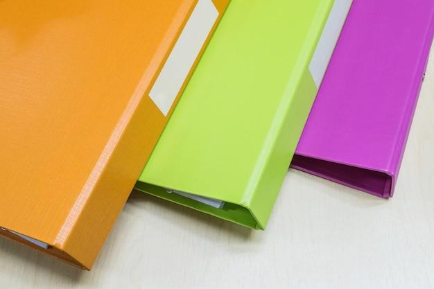 Closeup Groupe De Fichier De Document Coloré Sur Fond De Bureau Bois Photo Premium