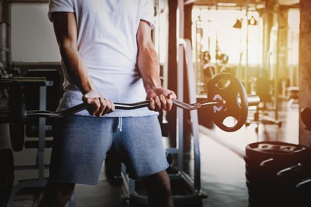 Closeup hommes en bonne santé tenant entraînement haltère et bâtiment du corps au fitness gym Photo Premium