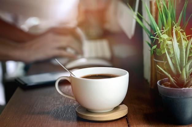 Closeup image de la tasse de café blanche sur teable en bois avec flou image de la main en tapant le clavier de l'ordinateur Photo Premium