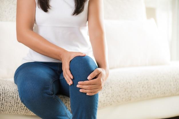 Closeup jeune femme assise sur le canapé et sensation de douleur au genou Photo Premium