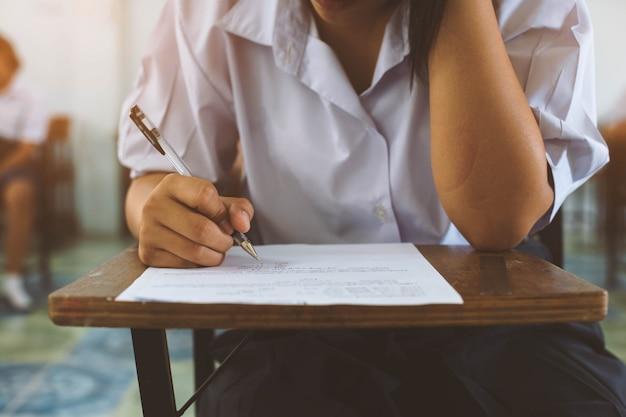 Closeup à la main de l'étudiant tenant un stylo et prenant un examen en salle de classe avec un stress pour le test de l'éducation. Photo Premium