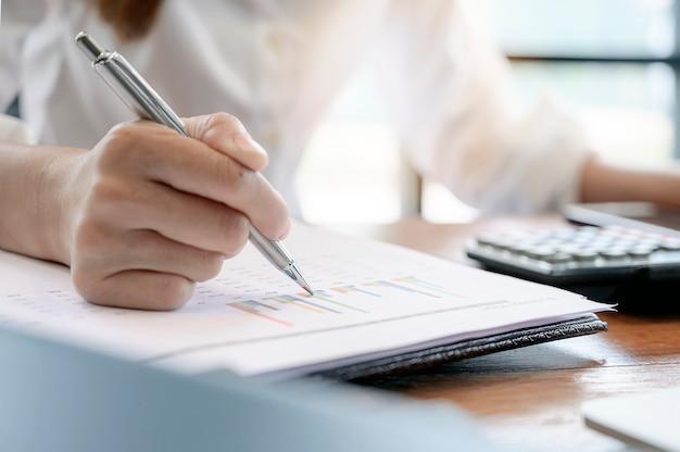 Closeup main féminine tenant un stylo pointant sur la paperasse Photo Premium