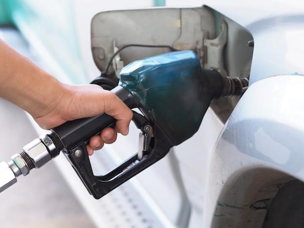Closeup main homme pompage d'essence dans la voiture à la station d'essence. Photo Premium