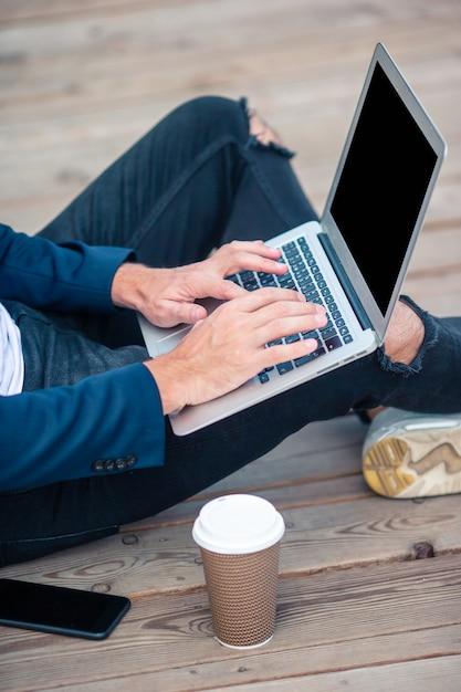 Closeup main d'homme travaillant sur un pont en bois avec ordinateur portable Photo Premium