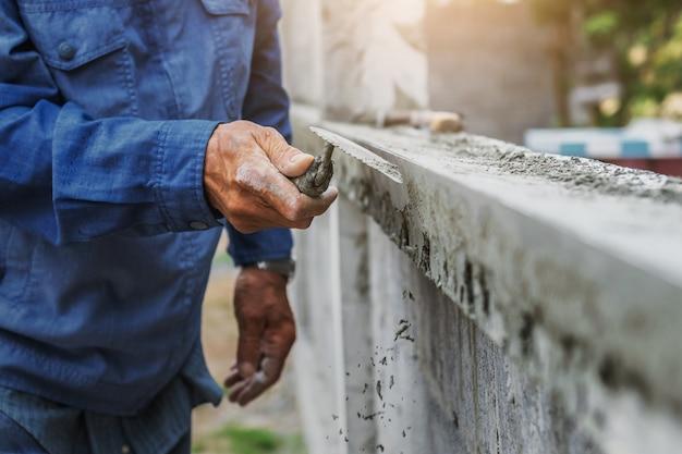 Closeup main d'ouvrier plâtrent Photo Premium