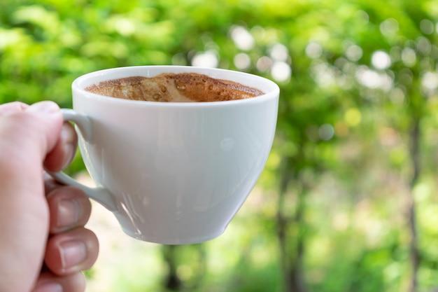 Closeup main tenant une tasse de café sur fond naturel du matin. Photo Premium