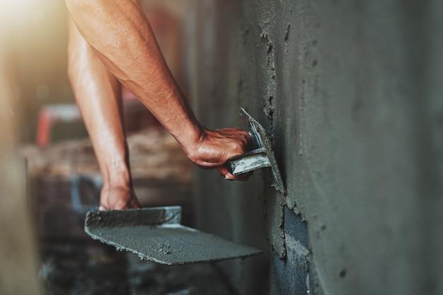 Closeup main de travailleur plâtrant du ciment au mur pour la construction d'une maison Photo Premium