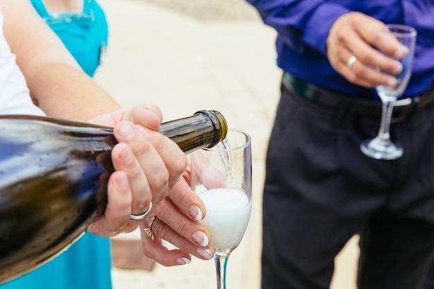 Closeup mains de la mariée et le marié avec des verres de champagne Photo Premium