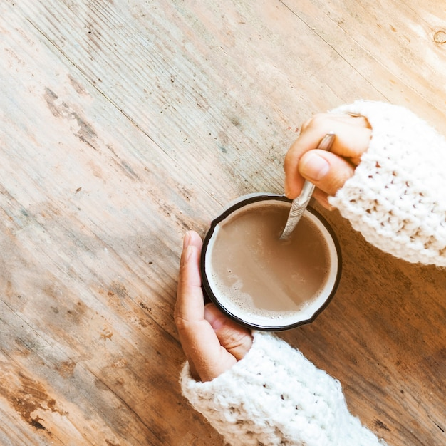 Closeup mains remuant le café dans la tasse Photo gratuit