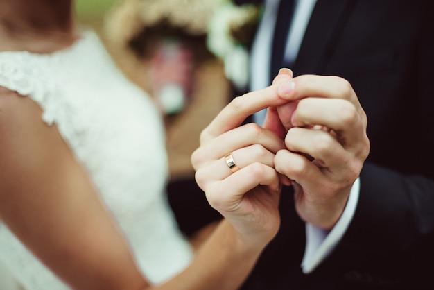 Closeup nouveaux mariés montrent leurs alliances en dansant Photo Premium