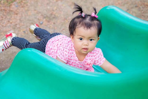 Closeup petite fille a menti sur le curseur vert au fond de l'aire de jeu Photo Premium