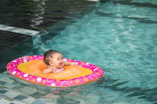 Closeup petite fille s'asseoir dans un bateau pour les enfants avec le visage souriant dans le fond de la piscine avec espace de copie Photo Premium