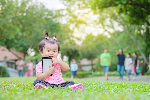Closeup petite fille s'asseoir sur le sol en herbe avec un téléphone portable à la main dans le parc avec fond clair du soleil en mouvement mignon Photo Premium
