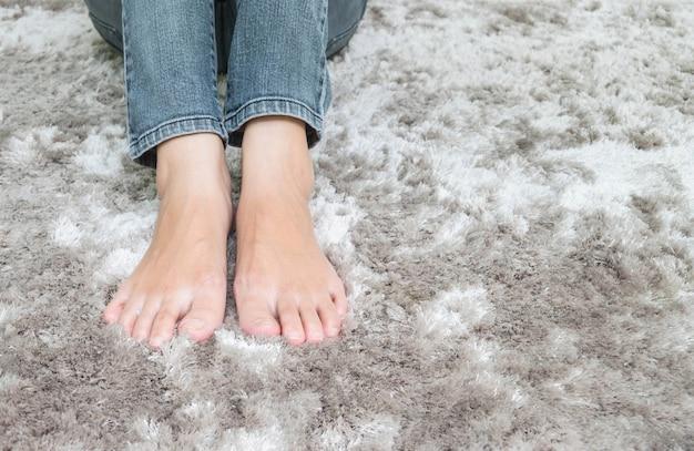 Closeup pied de femme asiatique assise sur un tapis gris sol fond texturé dans la maison Photo Premium