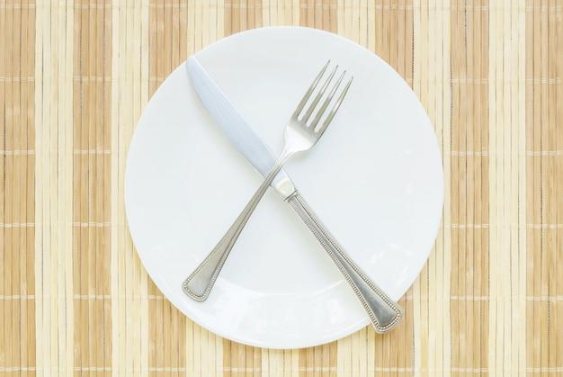 Closeup plat en céramique avec une fourchette et un couteau en acier inoxydable Photo Premium
