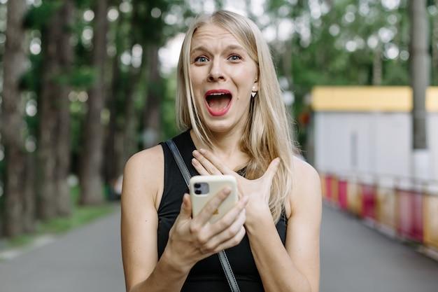 Closeup Portrait Anxieux Jeune Fille Regardant Téléphone Voir De Mauvaises Nouvelles Ou Des Photos Avec Une émotion Dégoûtante Sur Son Visage Isolé à L'extérieur Du Fond De La Ville. émotion Humaine, Réaction, Expression Photo Premium