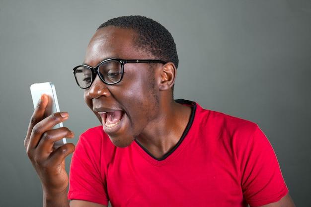 Closeup portrait de beau jeune homme en colère, mec, énervé étudiant, travailleur fou, employé, client insatisfait, criant au téléphone Photo Premium