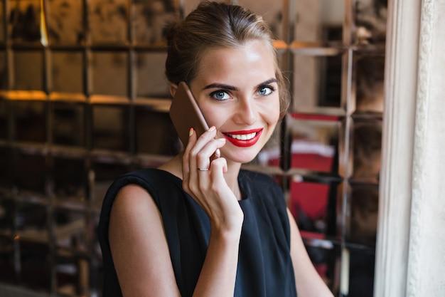 Closeup Portrait Beau Modèle à La Cafétéria. Elle Parle Au Téléphone, Souriant à La Caméra. Photo gratuit