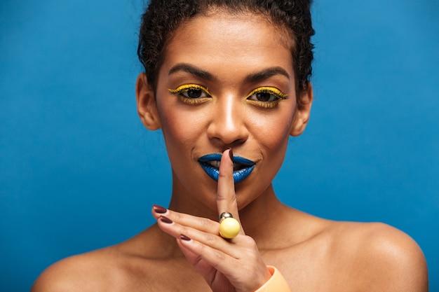 Closeup Portrait De Beauté D'une Femme Afro-américaine Incroyable Avec Le Maquillage De Mode Demandant De Garder Le Silence Ou De Mettre Le Doigt Secret Sur Les Lèvres Isolées, Sur Le Mur Bleu Photo gratuit