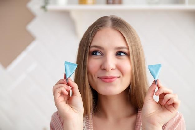Closeup portrait de belle jeune fille tenant des cosmétiques, des tubes avec la crème pour le visage, masque, sérum. Photo Premium