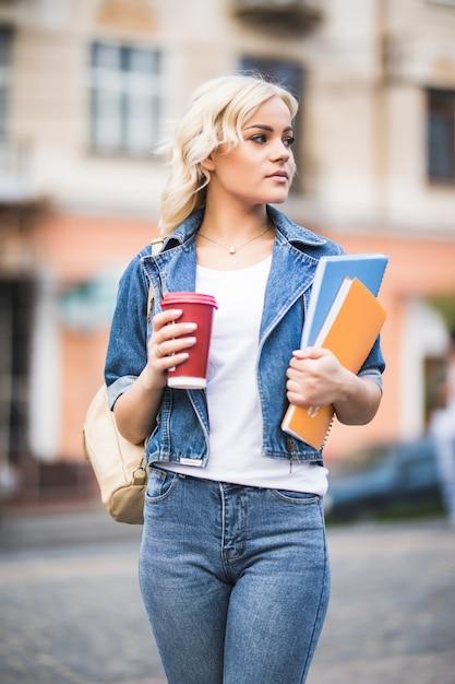 Closeup Portrait D'étudiant Fille Blonde Souriante Avec Beaucoup De Cahiers Habillés En Jeans Photo gratuit