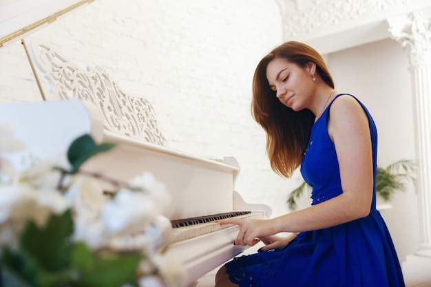 Closeup portrait d'une fille en robe bleue assis au piano et jouer du piano Photo Premium