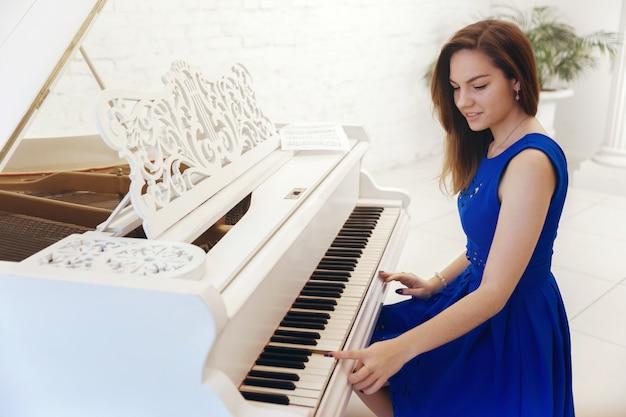 Closeup portrait d'une fille en robe bleue assis au piano et jouer du piano Photo Premium