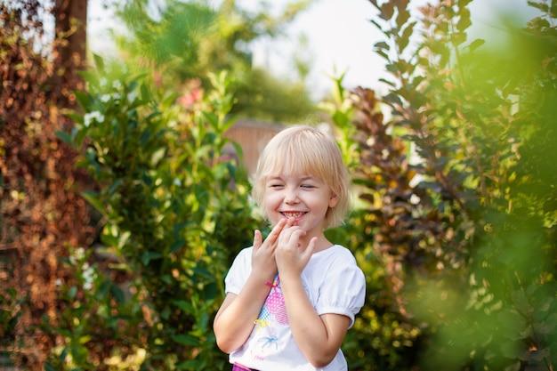 Closeup portrait de fillette blobde heureuse à l'école primaire en plein air dans un parc verdoyant Photo Premium