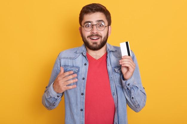 Closeup Portrait D'un Homme Barbu étonné Avec Carte De Crédit En Mains, Semble Excité, A Découvert Une énorme Somme D'argent Sur La Carte Photo gratuit