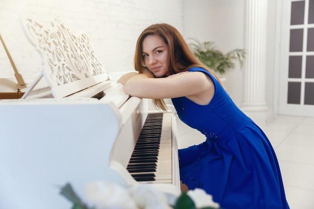 Closeup portrait d'une jeune fille en robe bleue assise au piano Photo Premium