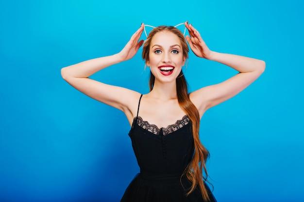 Closeup Portrait De Magnifique Blonde Prête Pour La Fête, Souriant Et Touchant Le Bandeau Avec Une Oreille De Chat En Diamants Vêtue D'une Belle Robe Noire, Maquillage Lumineux. Photo gratuit