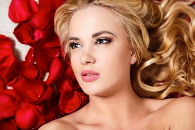 Closeup Portrait Of Beautiful Blond Dreaming Girl Avec Roses Rouges Longs Cheveux Bouclés Et Maquillage Lumineux Photo gratuit