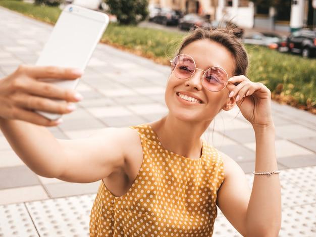 Closeup Portrait Of Beautiful Smiling Brunette Girl In Summer Hipster Yellow Dress. Modèle Prenant Selfie Sur Smartphone.femme Faisant Des Photos Dans Une Chaude Journée Ensoleillée Dans La Rue En Lunettes De Soleil Photo gratuit