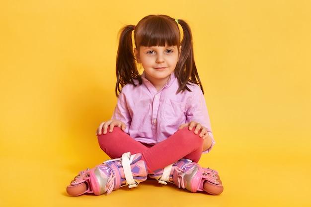 Closeup Portrait Of Calm Little Girl Sitting On Floor Avec Les Jambes Croisées Photo gratuit