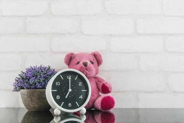 Closeup réveil pour décorer à 7h avec poupée ours et plante Photo Premium