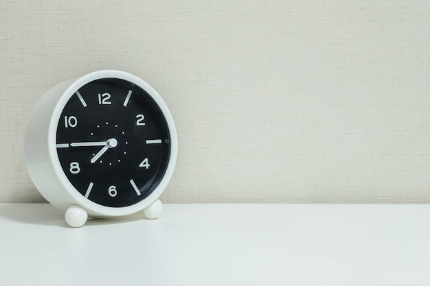 Closeup réveil pour décorer à huit heures moins le quart sur le bureau en bois Photo Premium
