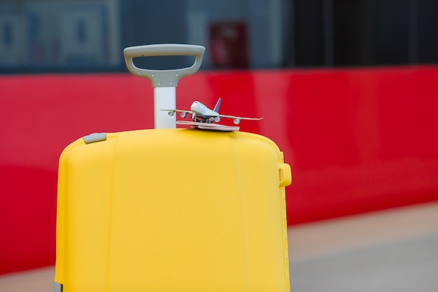 Closeup rouge passeports et avion petit modèle sur des bagages jaunes à la gare Photo Premium