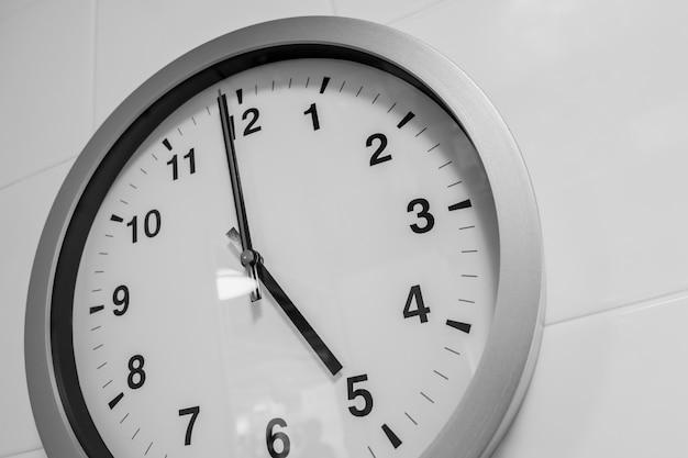 Closeup Simple Horloge Sur Le Temps Du Mur Blanc à 5 Heures Photo Premium