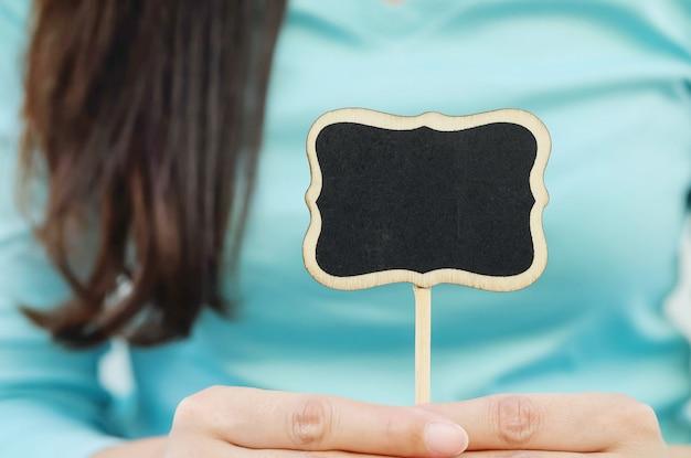 Closeup tableau en bois noir en forme de boîte de texte sur le corps flou de fond texturé femme Photo Premium