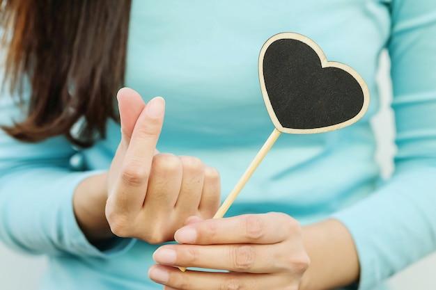 Closeup tableau en bois noir en forme de coeur avec le doigt de la femme en symbole mini coeur Photo Premium