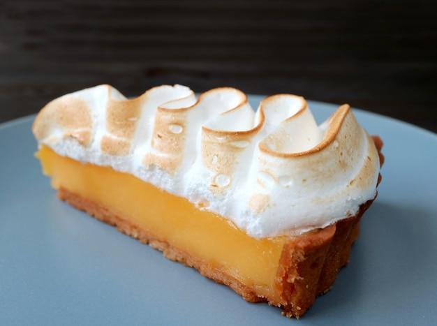 Closeup, une tranche de tarte meringuée au citron sur une assiette bleue Photo Premium