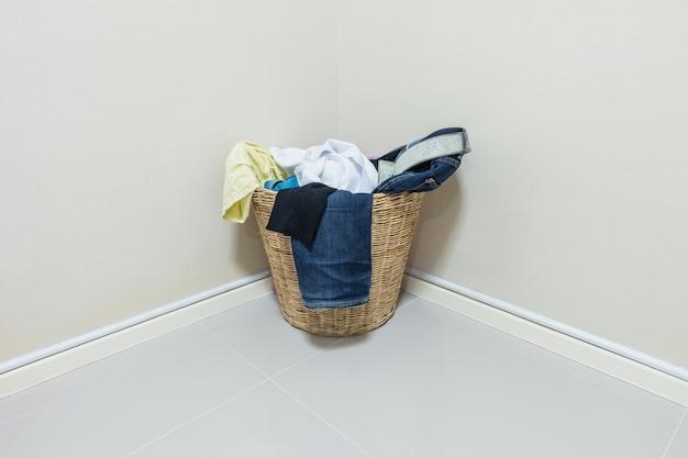 Closeup utilisé des vêtements dans un panier en bois au coin de la chambre Photo Premium