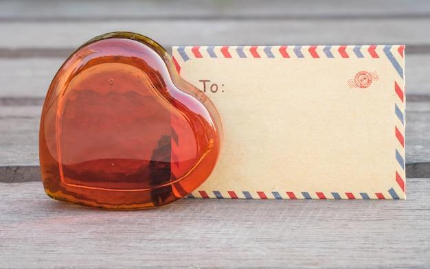 Closeup verre rouge en forme de coeur avec enveloppe brune sur une chaise en bois floue dans le thème de la saint-valentin Photo Premium