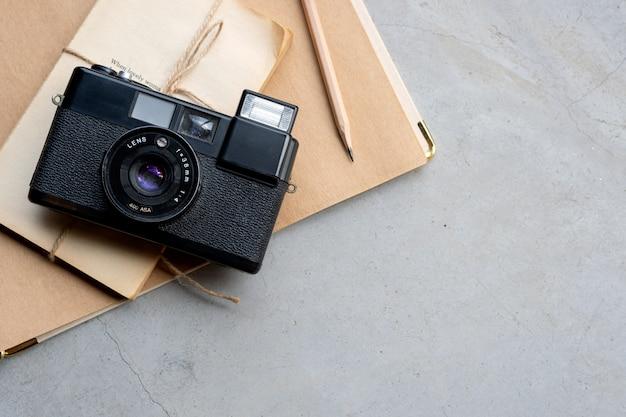 Closeup vintage camera et vieux cahier sur sol en ciment Photo Premium